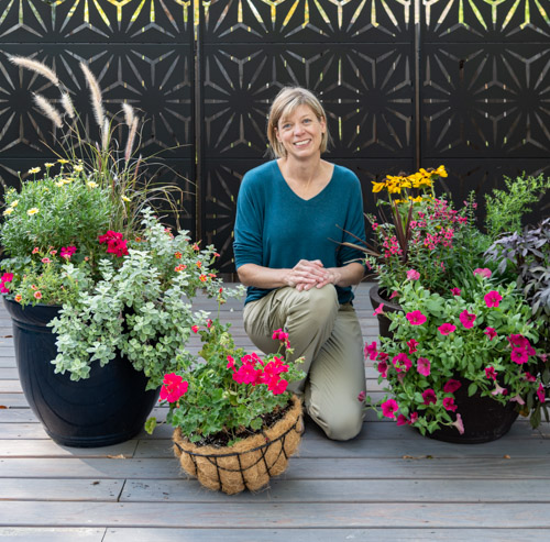 Ann from Go West Gardener with colorful flowerpots of flowers